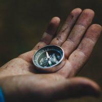 A hand holding a compass