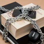 Laptop, book and smartphone chained together